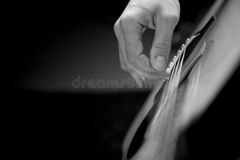 Concert acoustic guitarist. Acoustic guitar being played right hand stock photography