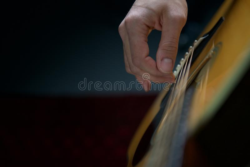 Concert acoustic guitarist. Acoustic guitar being played right hand royalty free stock photography