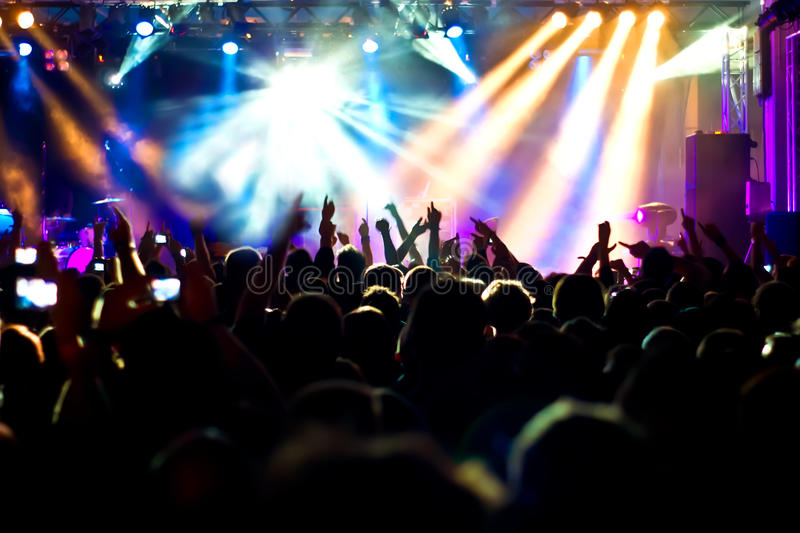 Concert Crowd. Cheering crowd at concert, bright yellow lights from stage royalty free stock images