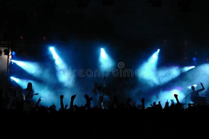 Concert Crowd. Cheering crowd at concert, musicians on the stage stock image