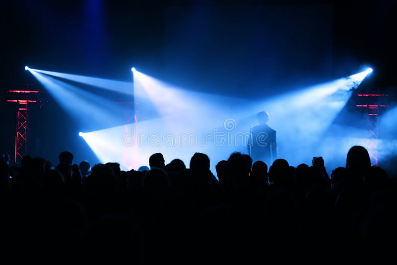 Concert Crowd. Cheering crowd at concert, musicians on the stage royalty free stock photos
