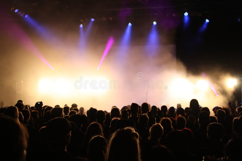 Concert Crowd. Cheering crowd at concert, musicians on the stage royalty free stock image