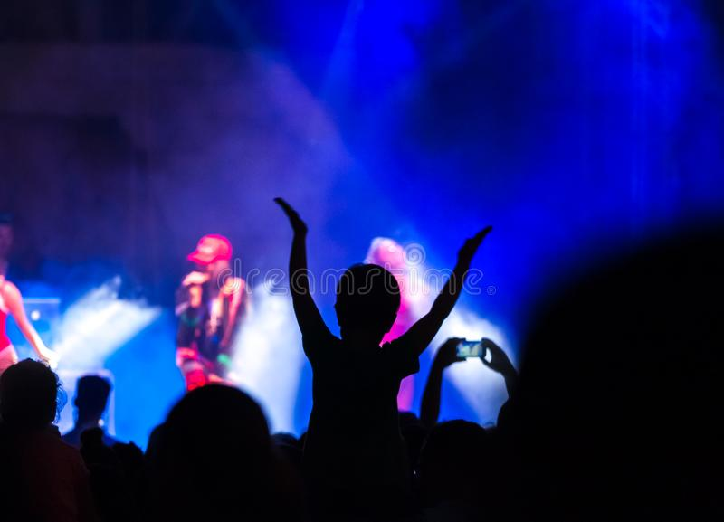 Concert crowd attending a concert, people silhouettes are visible, backlit by stage lights. Raised hands and smart phones are visi royalty free stock photo
