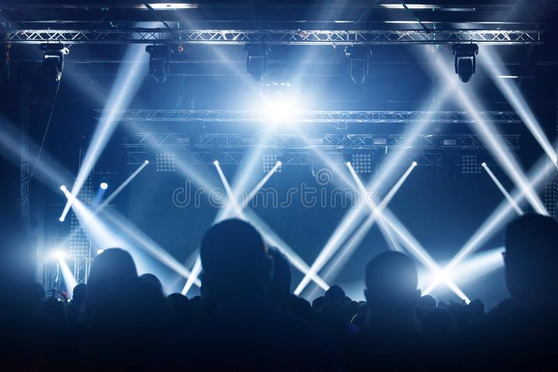 Concert crowd. People silhouettes in front of bright stage lights. Band of rock stars. stock images