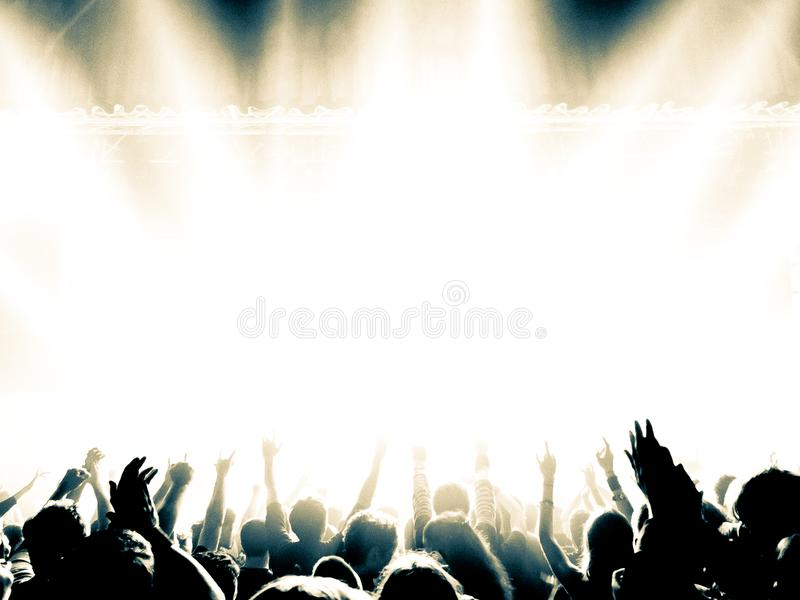 Concert crowd silhouettes in front of a bright stage royalty free stock photos