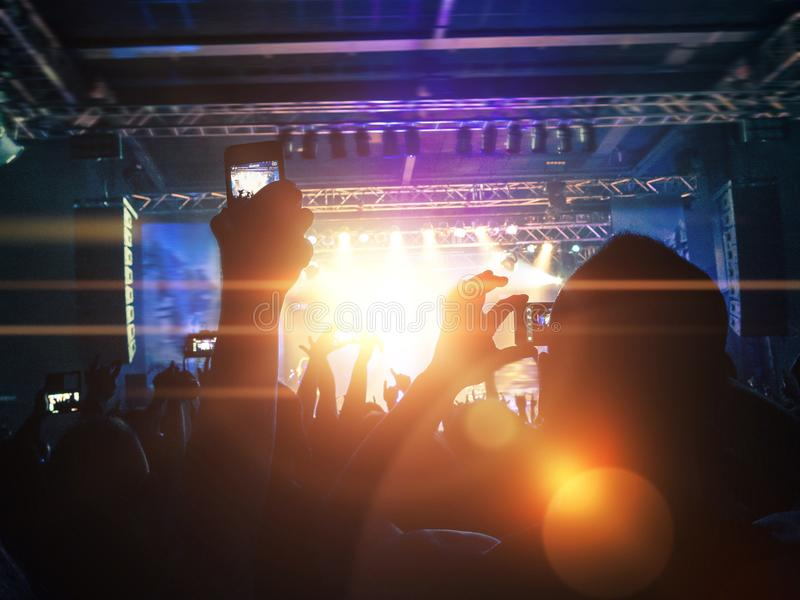 Concert crowd silhouettes in front of a bright stage royalty free stock image