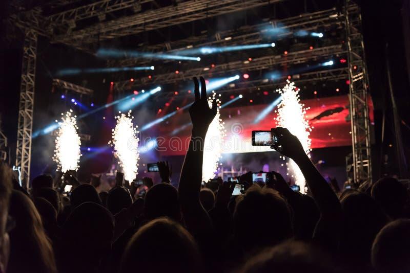 Concert de rock, silhouettes des personnes heureuses soulevant des mains photo stock