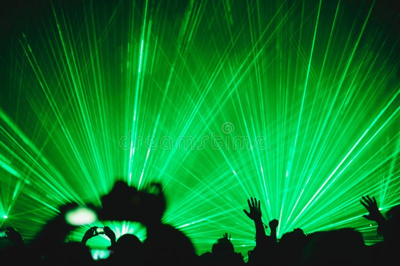 Green rays of lasers in the background of the crowd at a concert royalty free stock photo