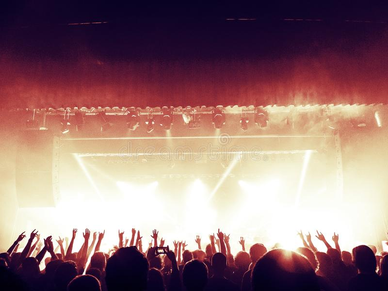 Concert crowd silhouettes in front of a bright stage stock photography