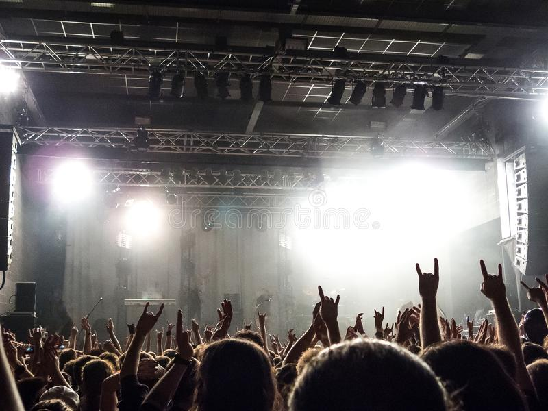 Concert crowd silhouettes in front of a bright stage royalty free stock photography