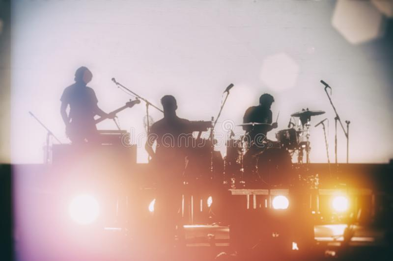 Concert of a musical rock band. Silhouettes of musicians on a se royalty free stock photos