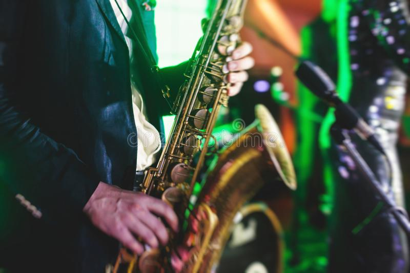 Concert view of a saxophone player with vocalist and musical jazz band in the background stock photos
