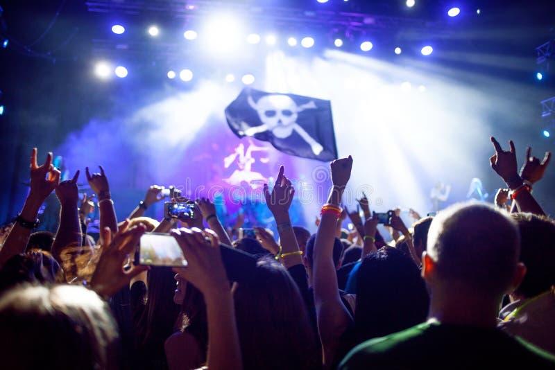 Concerto rock, le mani su La gente è felice nel club, bandiera di pirata davanti alle luci fotografie stock libere da diritti