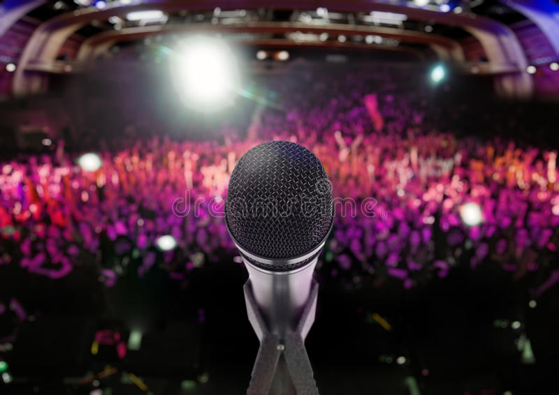 Concerts, music and related things. Microphone on stage with an audience on the background royalty free stock photo