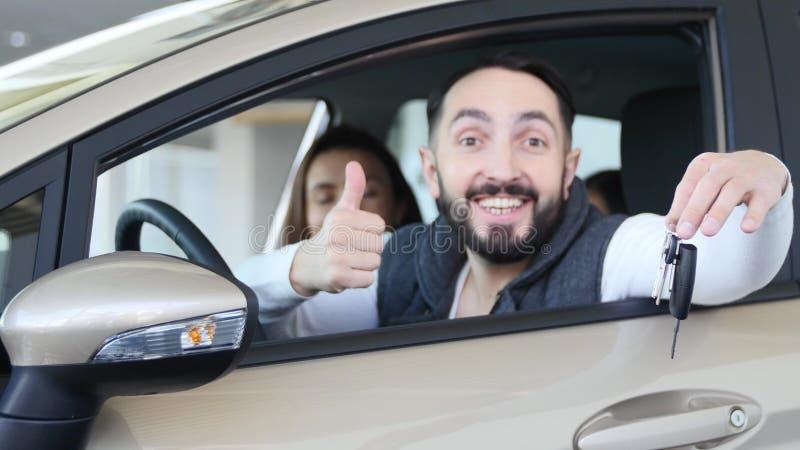 Concesión de coche que visita La familia hermosa es que habla y sonriente mientras que se sienta en su nuevo coche el hombre jove fotografía de archivo libre de regalías