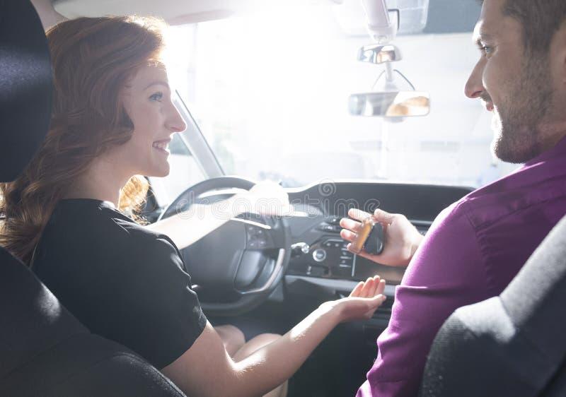 Concesionario de coches feliz que da llaves a la mujer sonriente durante la prueba de conducción imágenes de archivo libres de regalías