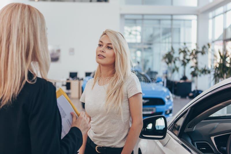 Concesionario de coches profesional que ayuda a su cliente femenino fotografía de archivo