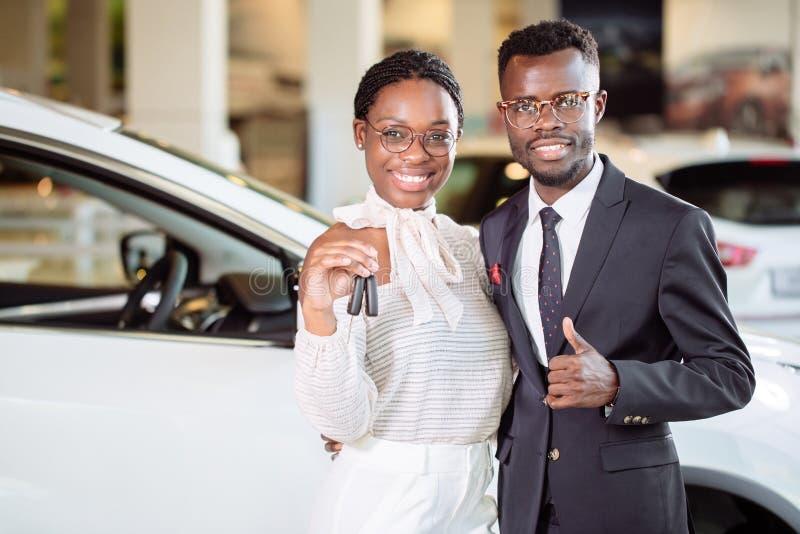 Concessionário automóvel de visita acople guardar a chave de seu carro novo, olhando a câmera imagens de stock royalty free