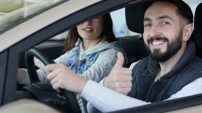 Concessionário automóvel de visita A família bonita é de fala e de sorriso ao sentar-se em seu carro novo o homem novo mostra o d fotos de stock royalty free
