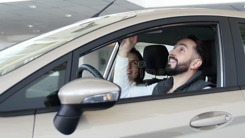 Concessionário automóvel de visita A família bonita é de fala e de sorriso ao sentar-se em seu carro novo o homem novo mostra o d fotos de stock