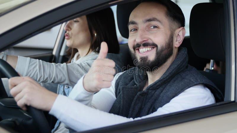 Concessionário automóvel de visita A família bonita é de fala e de sorriso ao sentar-se em seu carro novo o homem novo mostra o d fotografia de stock