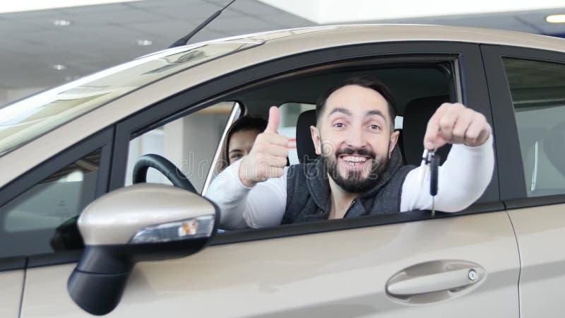 Concessionário automóvel de visita A família bonita é de fala e de sorriso ao sentar-se em seu carro novo o homem novo mostra o d imagens de stock