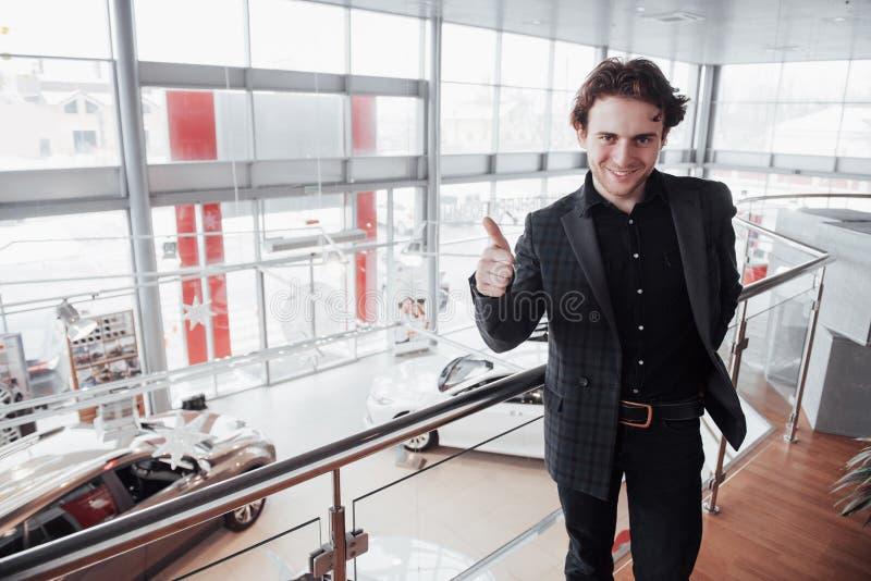Concessionário automóvel de visita Homem novo no fundo do salão de beleza do carro O homem feliz mostra o dedo acima Venda do car fotografia de stock