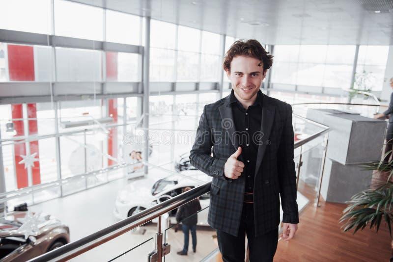 Concessionário automóvel de visita Homem novo no fundo do salão de beleza do carro O homem feliz mostra o dedo acima Venda do car foto de stock royalty free