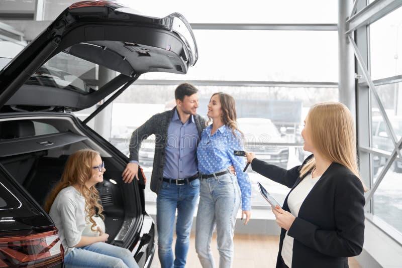 Concessionário automóvel fêmea que dá às chaves do carro dos compradores imagem de stock royalty free