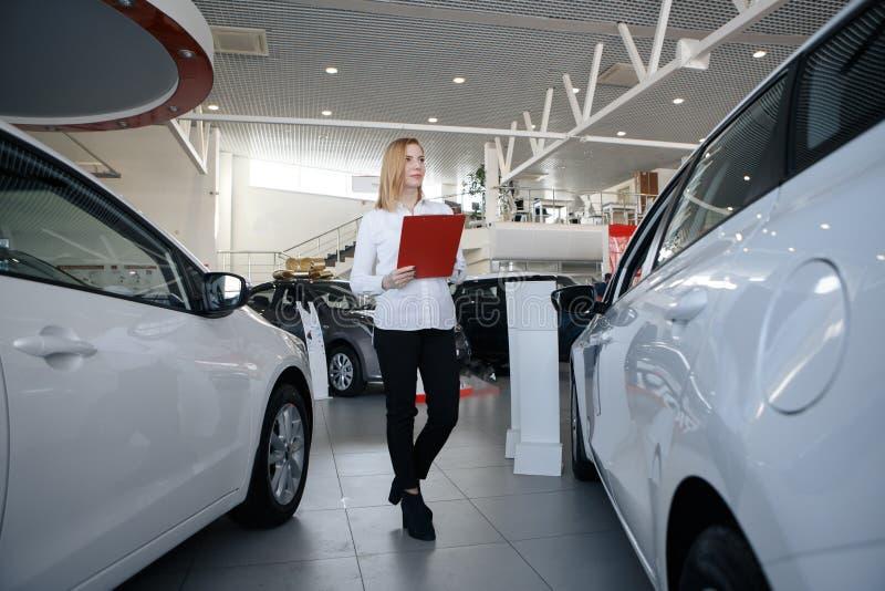 Concessionário automóvel feliz da mulher no auto salão de beleza que olha originais fotos de stock