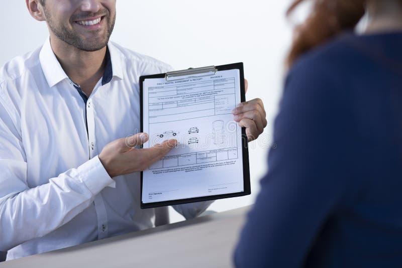 Concessionário automóvel profissional de sorriso que mostra o acordo alugado e o recibo diários ao comprador imagem de stock