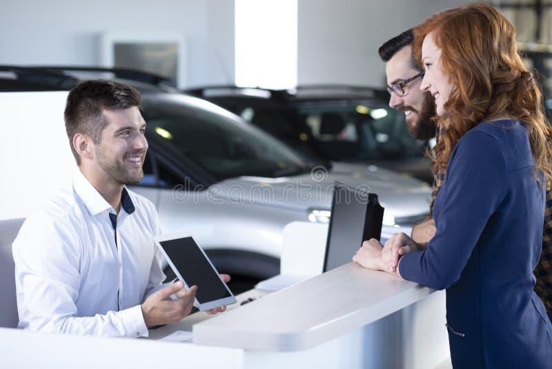 Concessionário automóvel profissional de sorriso que mostra uma oferta aos compradores felizes imagem de stock