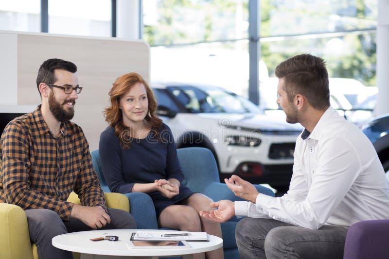 Concessionário automóvel profissional que fala com os compradores na sala de exposições exclusiva fotografia de stock