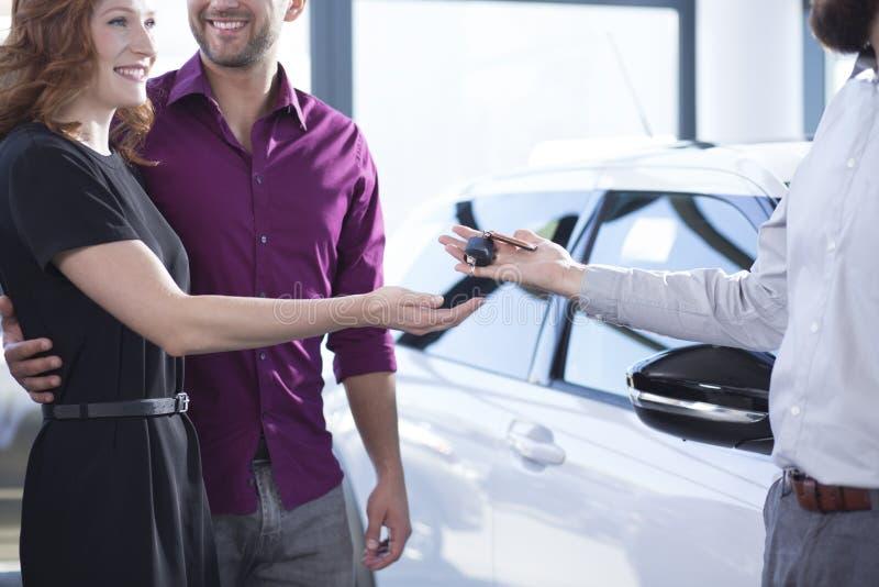 Concessionário automóvel que dá chaves à mulher feliz e ao homem de sorriso em um deali fotos de stock