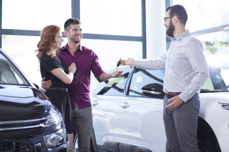 Concessionário automóvel que dá chaves do carro a um casal feliz imagens de stock