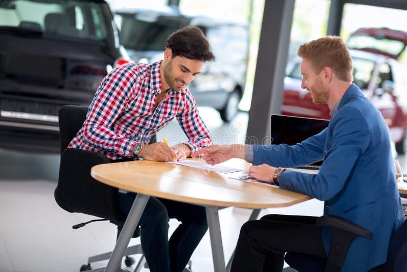 Concessionário automóvel que explica o contrato de vendas ao homem que compra um carro imagem de stock royalty free