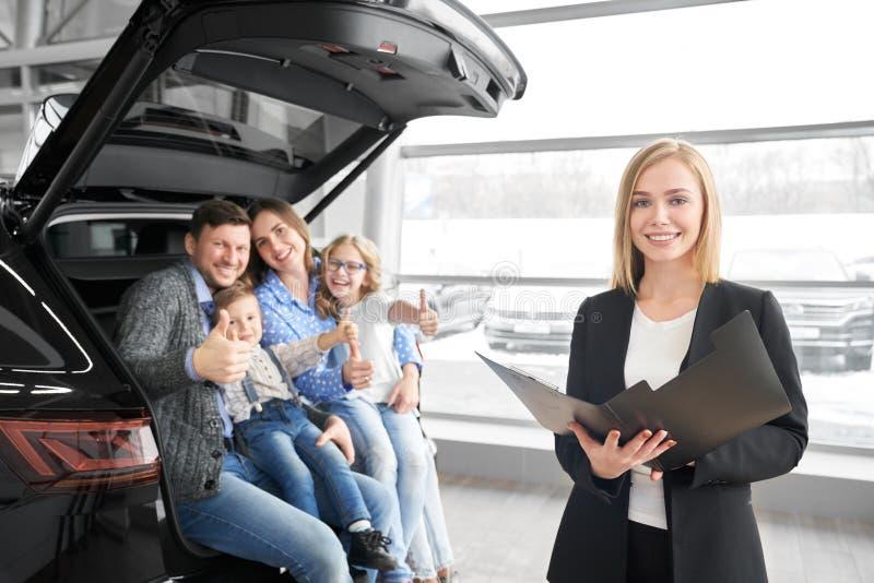 Concessionário automóvel que levanta na câmera com família, compradores do carro novo fotos de stock