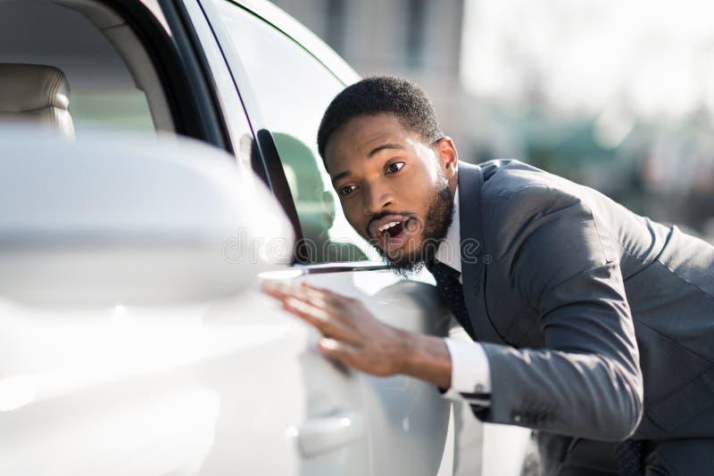 Concession?rio autom?vel de visita Homem do Afro que abraça seu carro novo foto de stock