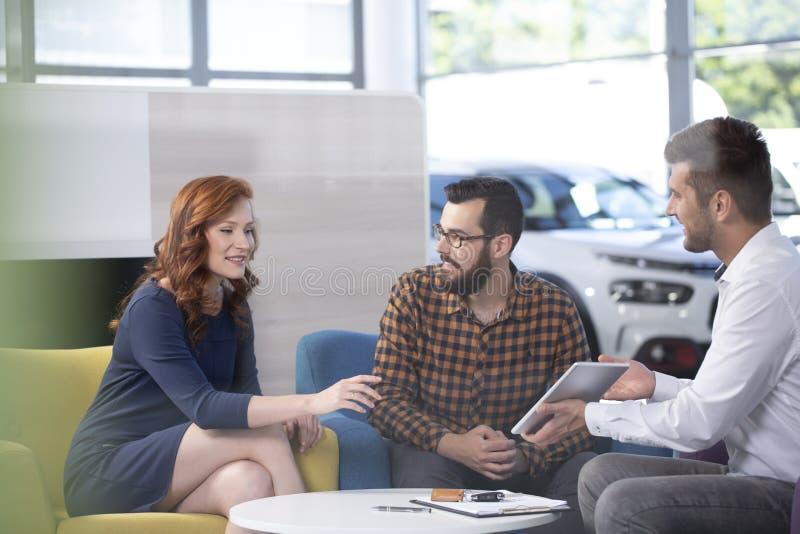 Concessionnaire automobile professionnel offrant les véhicules luxueux pendant le meeti image libre de droits