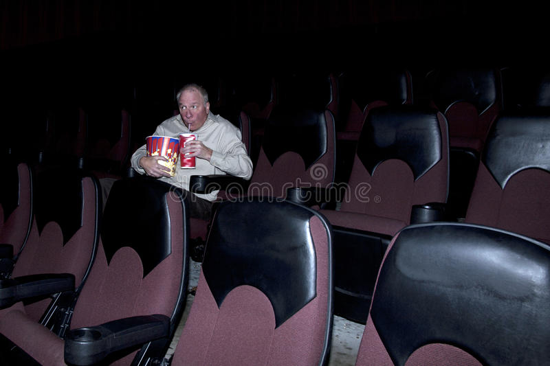 Man Enjoying Concessions in Movie Theater royalty free stock photography