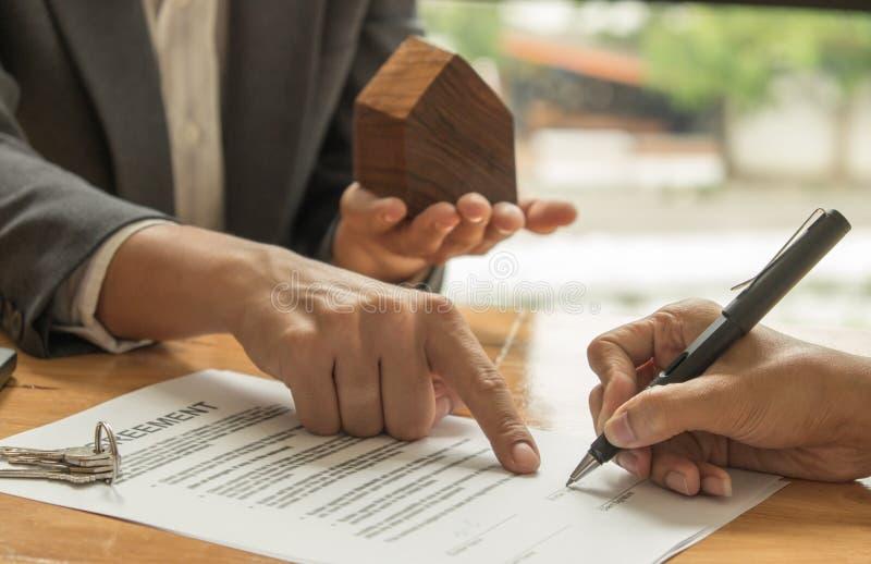 Concetti commerciali del bene immobile, mediatori domestici e compratori firmanti una s fotografia stock