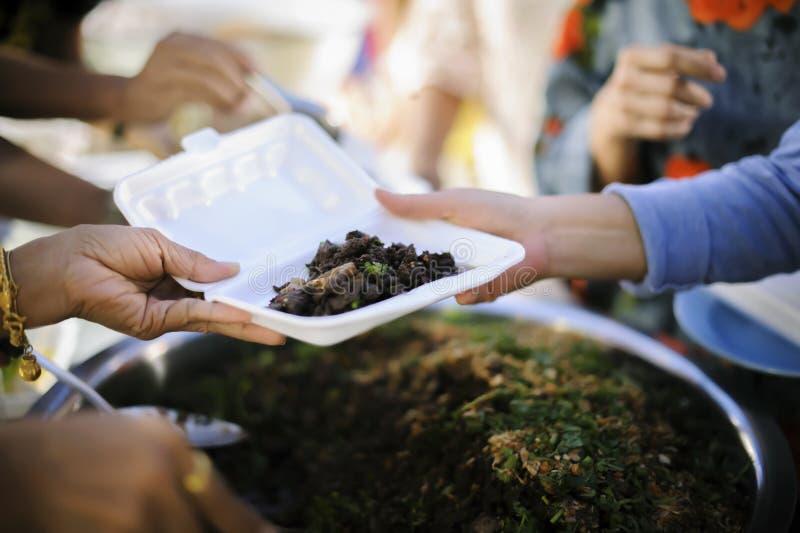 Concetti d'alimentazione: La mano ha offerto donare l'alimento da una parte dell'uomo ricco: Il concetto di divisione sociale: Ge fotografia stock libera da diritti