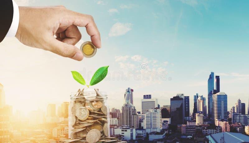 Concetti dei soldi di risparmio, mano dell'uomo d'affari che mette moneta in barattolo di vetro, con la pianta che cresce, città  immagini stock libere da diritti
