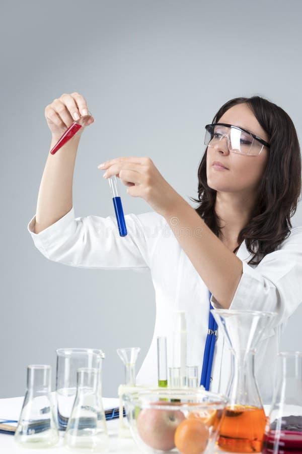 Concetti di scienza e della medicina Ricercatore femminile caucasico Compares Substances in due boccette separate immagini stock