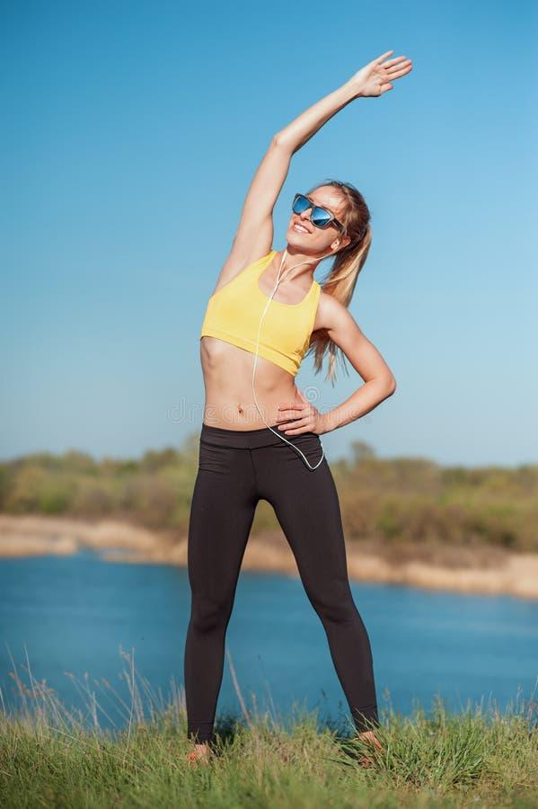 Concetti sani di sport e di stile di vita La donna in abiti sportivi ed occhiali da sole alla moda sta facendo l'esercizio sulla  fotografie stock libere da diritti