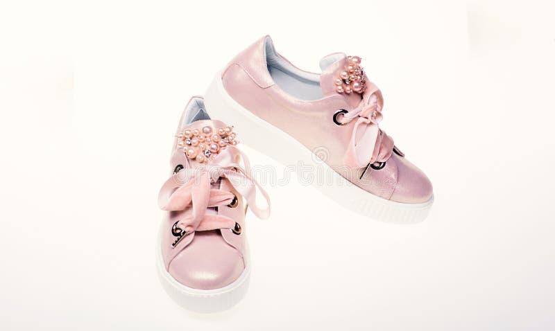 Concetto affascinante delle scarpe da tennis Le calzature per le ragazze e le donne decorate con la perla bordano Paia di pallido immagini stock libere da diritti