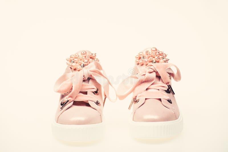 Concetto affascinante delle scarpe da tennis Scarpe sveglie isolate su fondo bianco Calzature per le ragazze e le donne decorate  fotografia stock libera da diritti