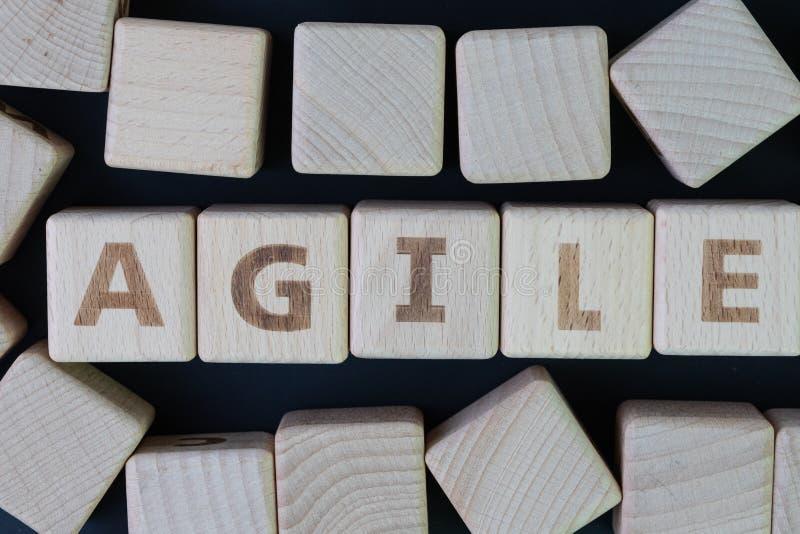 Concetto agile di sviluppo di software, blocchetto di legno del cubo con l'alfabeto che sviluppa la parola agile al centro sulla  fotografie stock