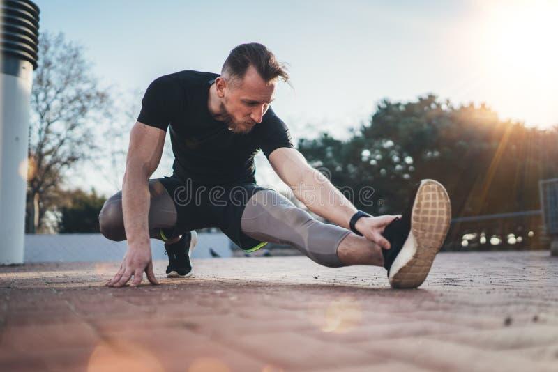 Concetto all'aperto di stile di vita di allenamento Il giovane uomo di forma fisica che fa l'allungamento esercita i muscoli prim immagine stock