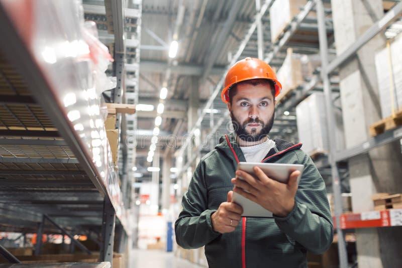 Concetto all'ingrosso, logistico, della gente e dell'esportazione - responsabile o supervisore con la compressa al magazzino immagini stock